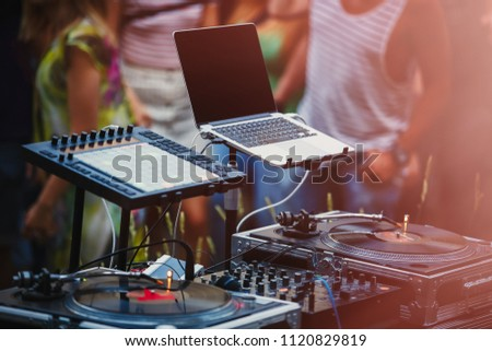 Open air music festival stage equipiment.DJ setup for playing music set on dance party.People dancing on background at backyard party.Disc jockey setup with midi controller & vinyl records player #1120829819
