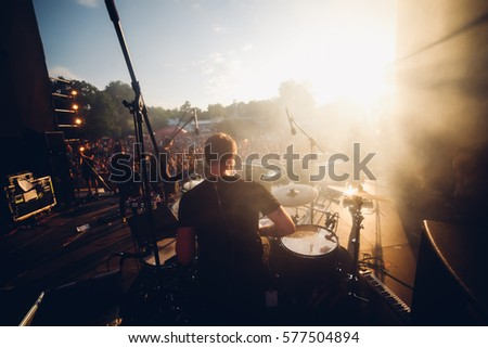 Shutterstock Open air view from the stage to the drummer and another band mates in sunset warm lights. Stage smoke, sun rays in it. Silhouettes of the summer festival