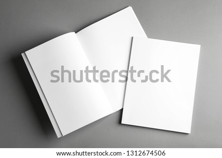 Open and closed blank brochures on grey background, top view. Mock up for design #1312674506