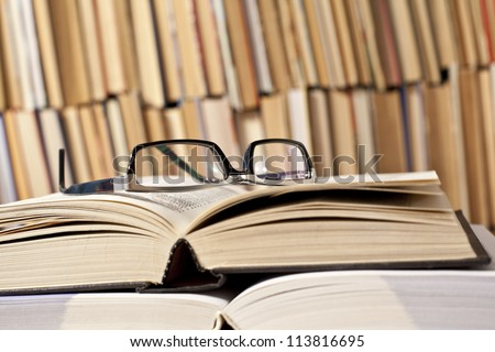 open and closed books and black glasses on  table front of a full bookshelf September 1st - the day of knowledge symbol of vision loss and eye strain from long reading