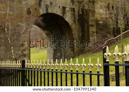 Open arch in a damp, sandstone, 19th century bridge behind ornate, black railings, topped by golden painted finials in shape of splayed trident, against grassy hill with fallen tree and young trees. #1047991240