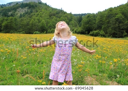 Open arms girl in beautiful flower spring meadow in Pyrenees mountains Spain
