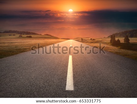 Open asphalt road towards the setting sun in beautiful countryside landscape.