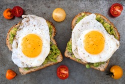 Open avocado, egg sandwiches on whole grain bread with tri-colored tomatoes on rustic baking tray