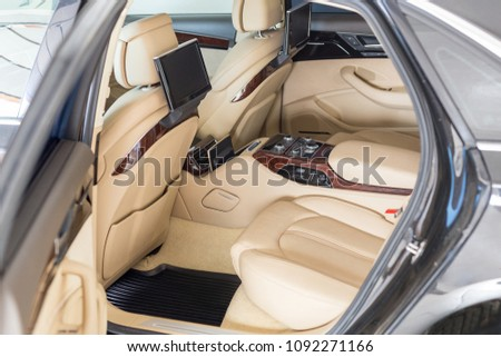 Open back door of business class car. Rear seat of modern luxury vehicle. Interior of limousine with entertainment system climate control and facilities for comfort. Rent  car with driver concept