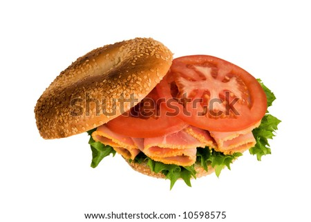 Open bagel filled with ham and salad on isolated white background