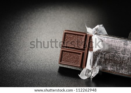 Open bar of chocolate on a black textured background