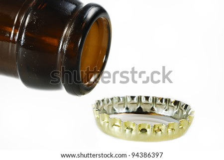Open beer bottle and a crown cap