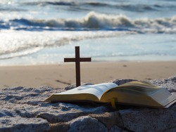 Open bible  and wood holy cross on stone with  blue sea as background. Love study bible.Bible is guide book of life. Christianity background concept.