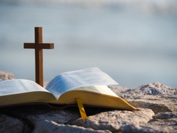 Open bible  and wood holy cross with  blue sea as background. Love study bible , holy book , Christianity concept.