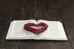 Open Bible book on a wooden table. Red heart.