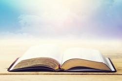open bible on wooden table over cloudy blue sky background