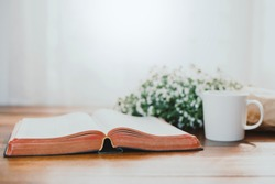 open bible with acup of coffee over flower on wooden table