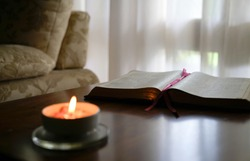 Open bible with burning candle on the table. Cosy home environment.