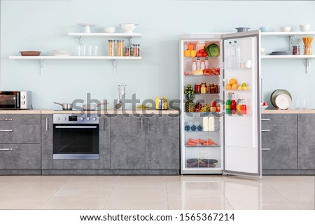 Open big fridge with products in interior of kitchen