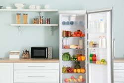Open big fridge with products in kitchen