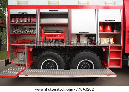 Open big red fire engine equipped with fire cocks and hoses at day