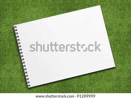 open binder notebook on grassland with empty page.