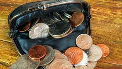 Open black leather pocket wallet full of various coins. Financial crisis, poverty, lack of money. On wooden background or table. Close-up.