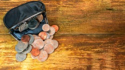 Open black leather pocket wallet full of various coins. Financial crisis, poverty, lack of money. On wooden background or table. Flat lay. Top view. Close-up.