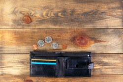 Open black leather pocket wallet with coins one cent and a quarter dollar nearby. Financial crisis, poverty, lack of money. On wooden background or table. Flat lay. Top view. Close-up.