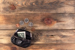 Open black leather pocket wallet with coins one cent, quarter dollar and 2 dollars banknote nearby. Financial crisis, poverty, lack money. On wooden background or table. Flat lay. Top view. Close-up.