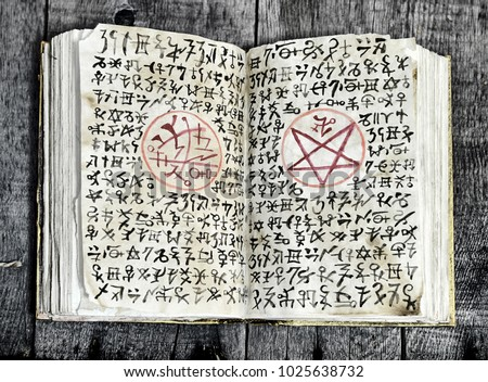 Stock Photo Open black magic book with evil symbols and pentagram on shabby pages. Halloween, occult, esoteric and wicca concept. Vintage background