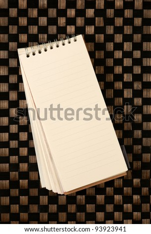 Open blank note book on bamboo texture - stock photo