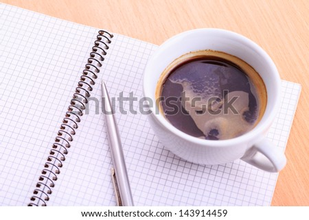 Open blank note book with coffee cup and a pen on wood table