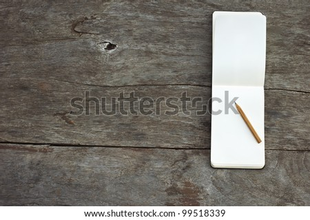 Open blank notepad with empty white pages with a pencil laying on a wooden table horizontal