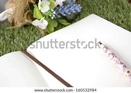 open blank paper page with pen on grass