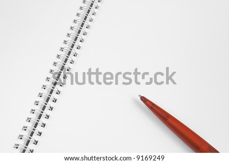 Open, blank spiral notebook with red plastic pen.