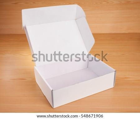 Open blank white box mock up on wood background.