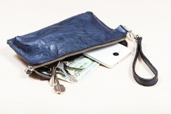open blue leather wristlet purse bag with bunch of keys, smartphone and euro banknotes on pale brown table
