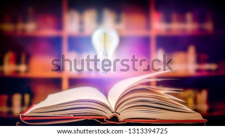 Open book and glowing light bulb over it In a library with a blurred bookshelf background Knowledge, education concept #1313394725