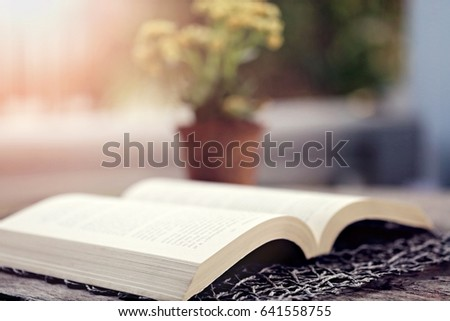 Open book closeup on wooden table outdoor leisure with soft focus and blur background #641558755