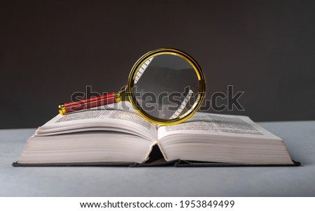 Open book closeup with turning pages and magnifying loupe. Textbook in hard cover on table. Studying and research concept. Foto stock ©