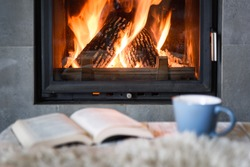 Open book, cup of tea and warm plaid near burning fireplace. Hygge concept