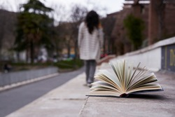 Open book forgotten on a stone seat and a woman walking away unfocused.