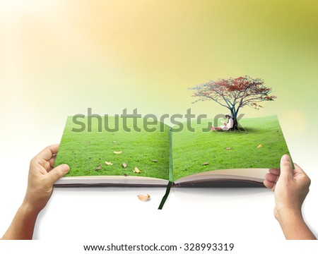 Open book in a beautiful asian girl reading book under red big tree on blurred autumn sunset background.