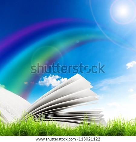 Open book in green grass over blue sky. Magic book
