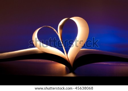 Open book in red heart shape on blue background
