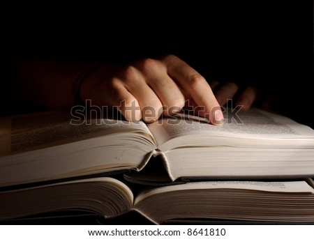 Open book in the dark with a hand