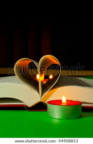 Open book laying on the table with burning candle