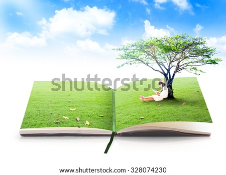 Open book of nature in a beautiful asian girl reading book under big tree on green meadow over blue sky background.