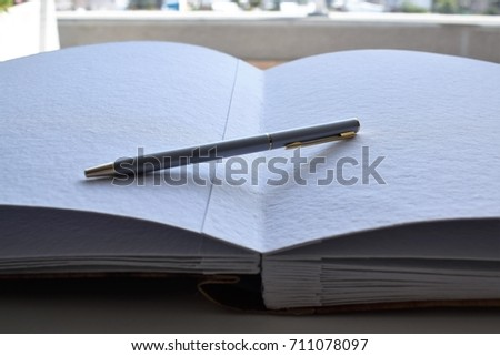 Open book of recycled paper and wood cover with a pen over it #711078097