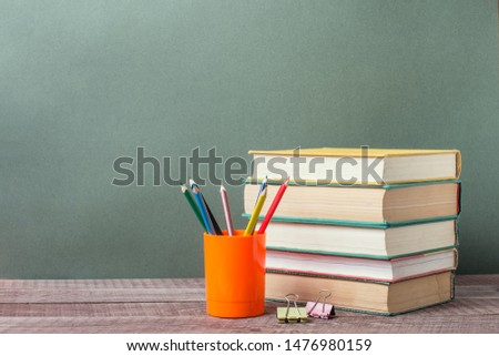 Open book, old textbooks, colored pencils on wooden table on paper green background.