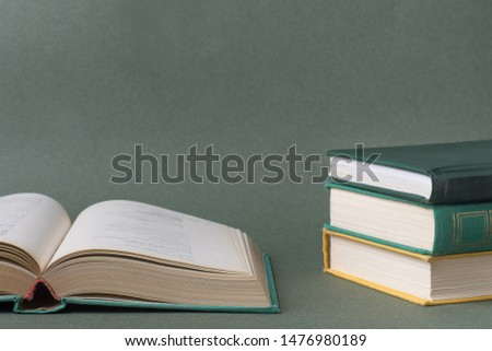 Open book, old textbooks, on paper green background.