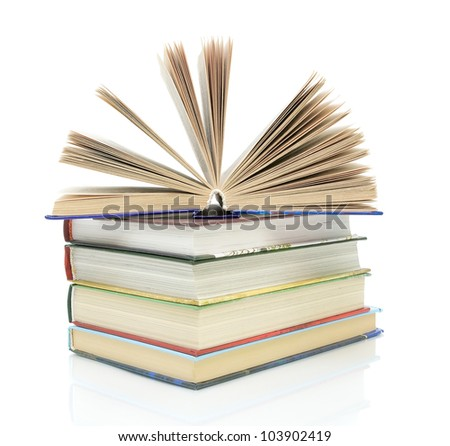 open book on a pile of books on a white background with reflection closeup