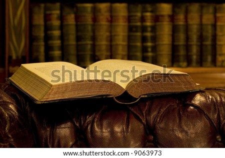 Open book on leather old couch